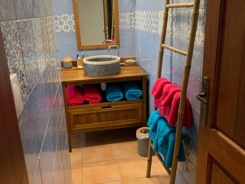 Salle de douche avec serviettes et tapis de bain. Produits d'accueil offerts. À disposition sèche cheveux, chargeur de brosse à dents électrique Braun ainsi qu'une brosse électrique à brushing.